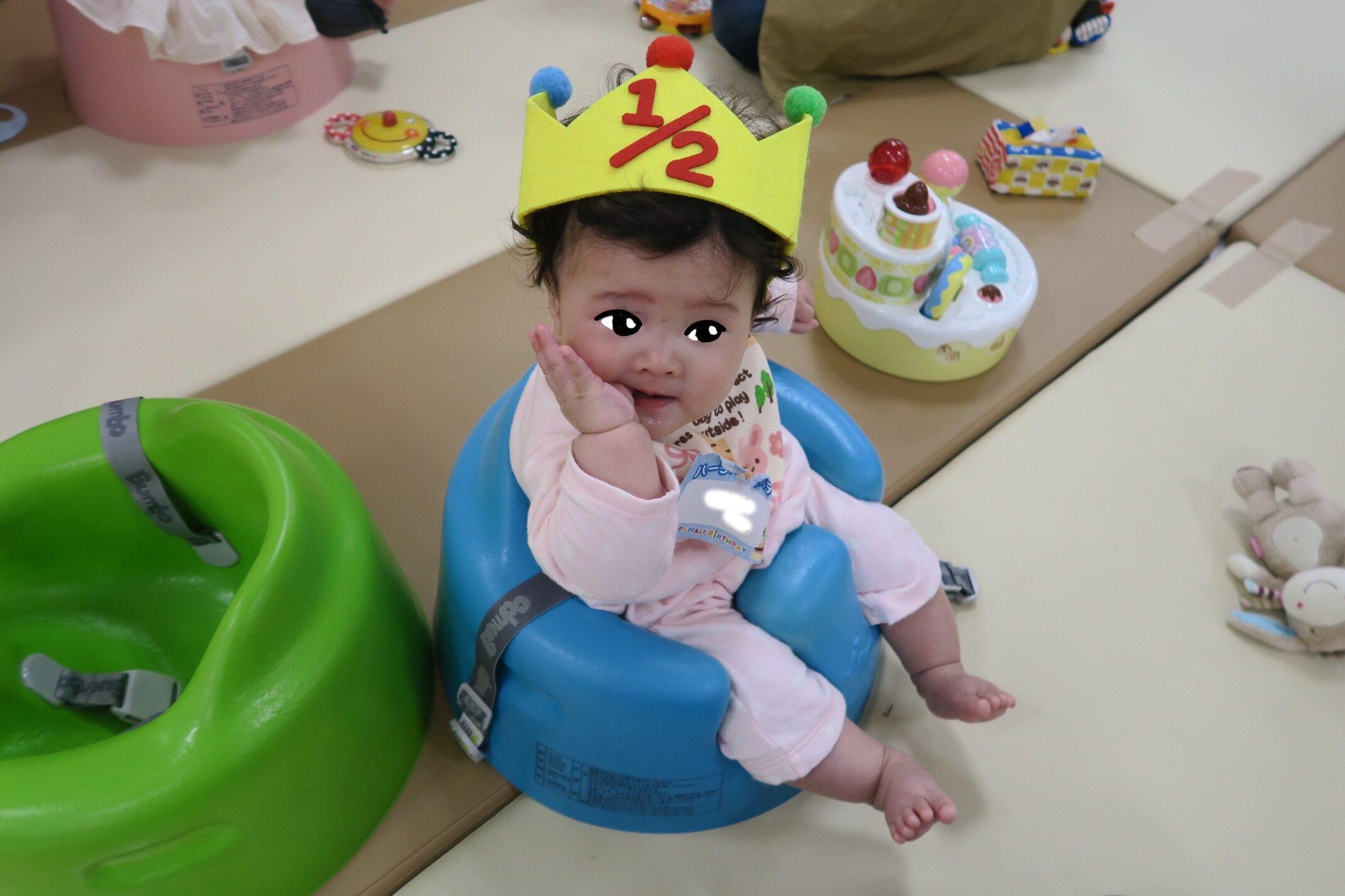 バンボに座る生後6か月の赤ちゃん